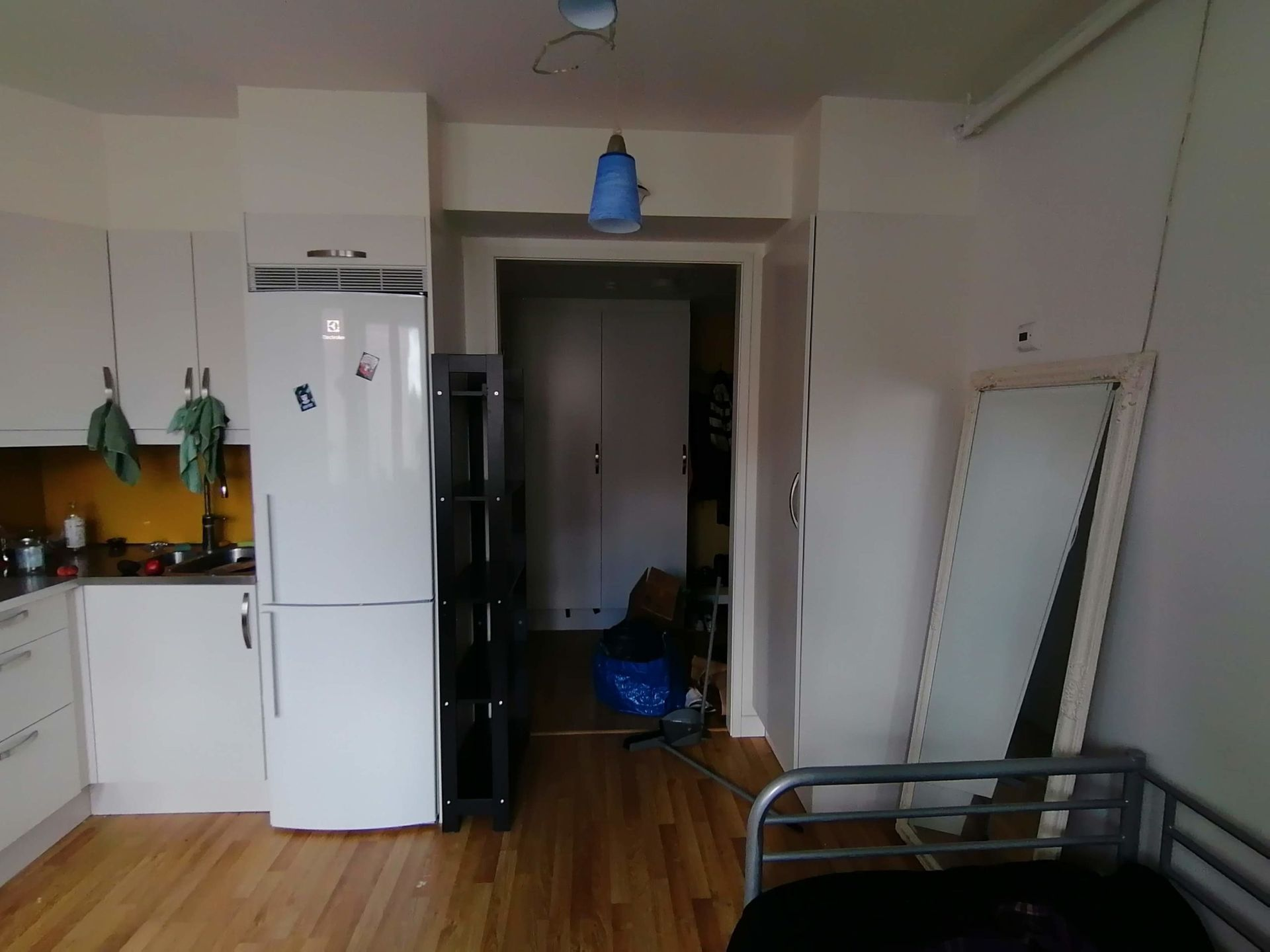 A door frame next to a fridge in an apartment