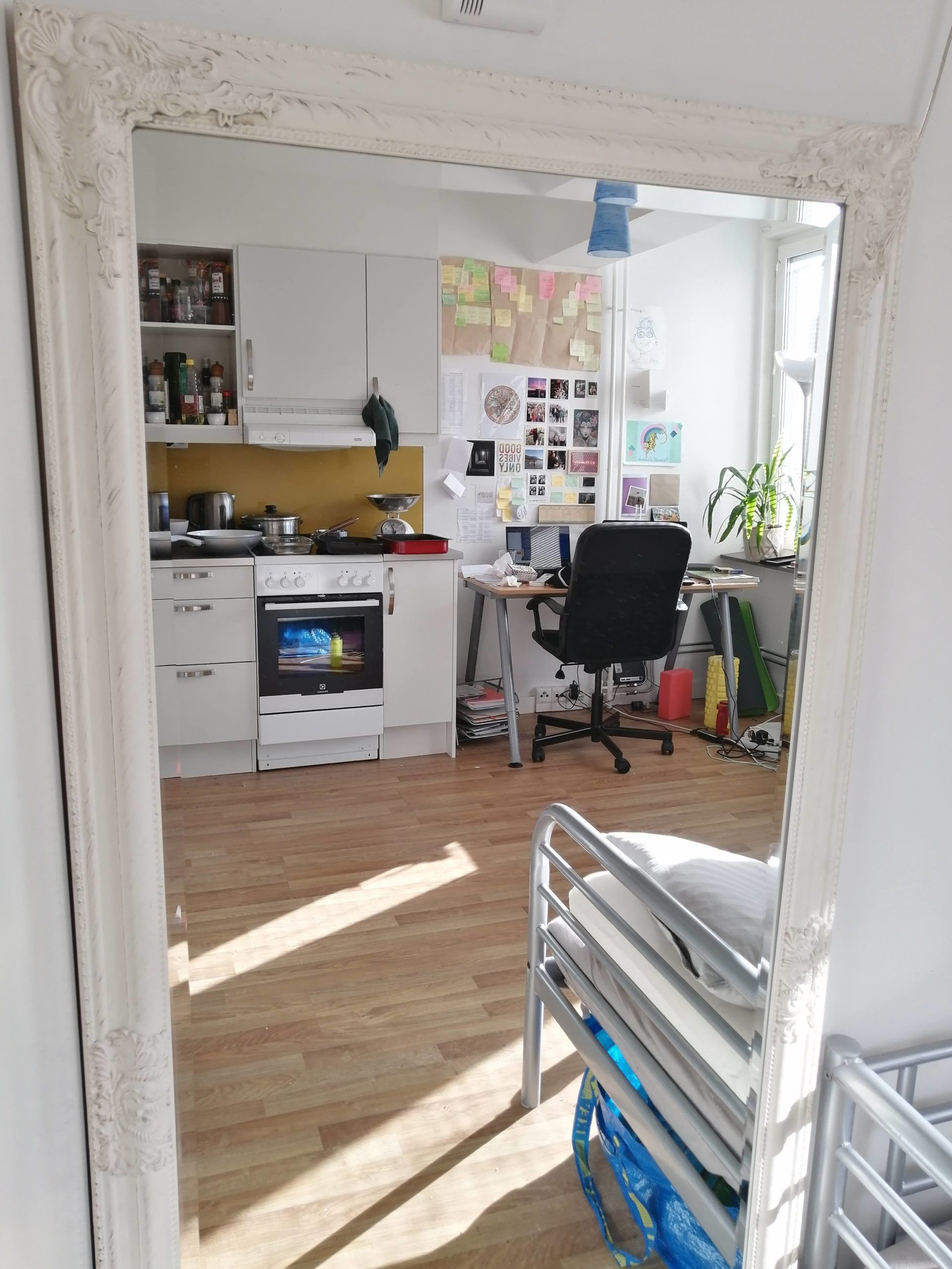 A mirror reflecting a room in an apartment