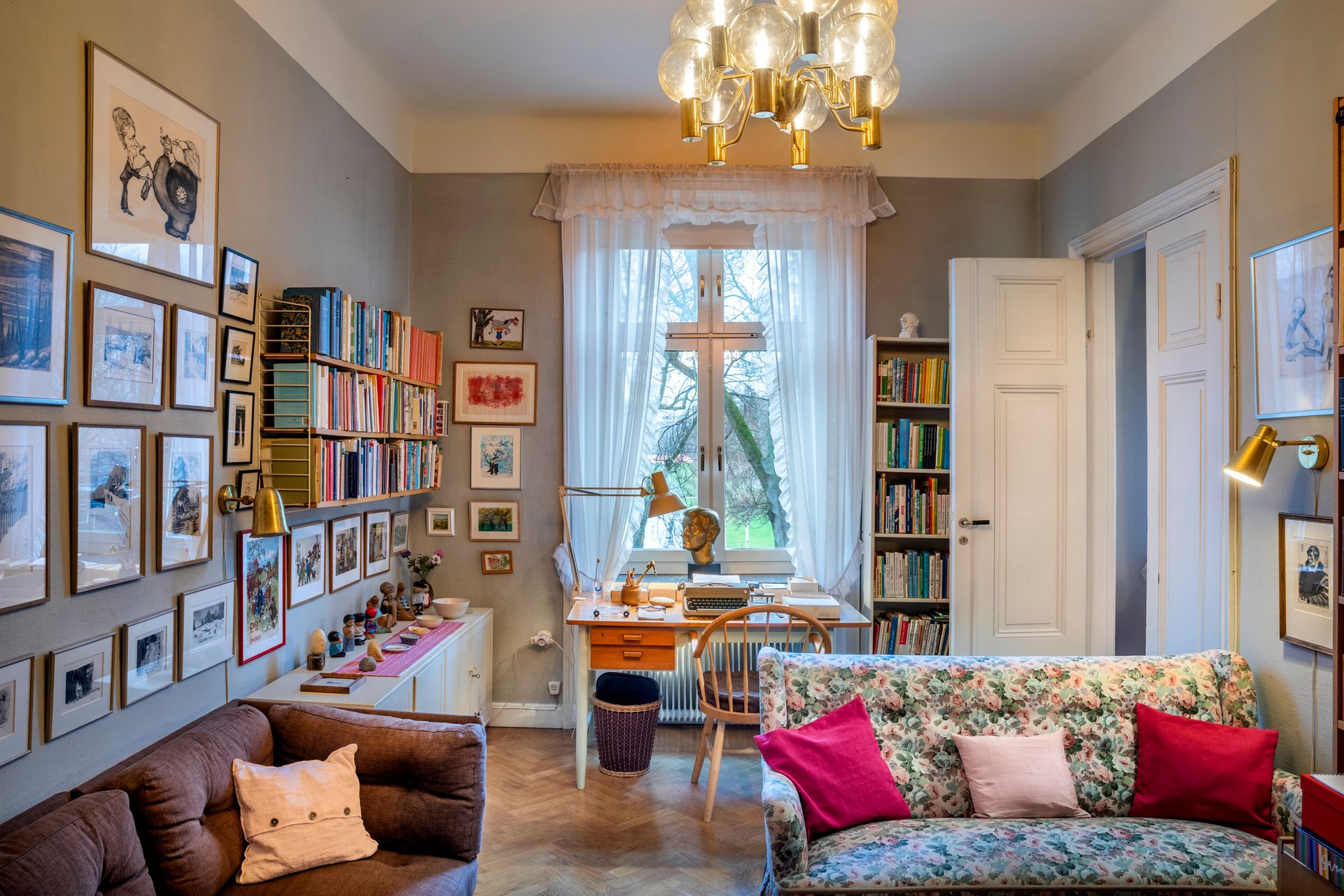 A cozy flat with bookshelf, posters, and a big window