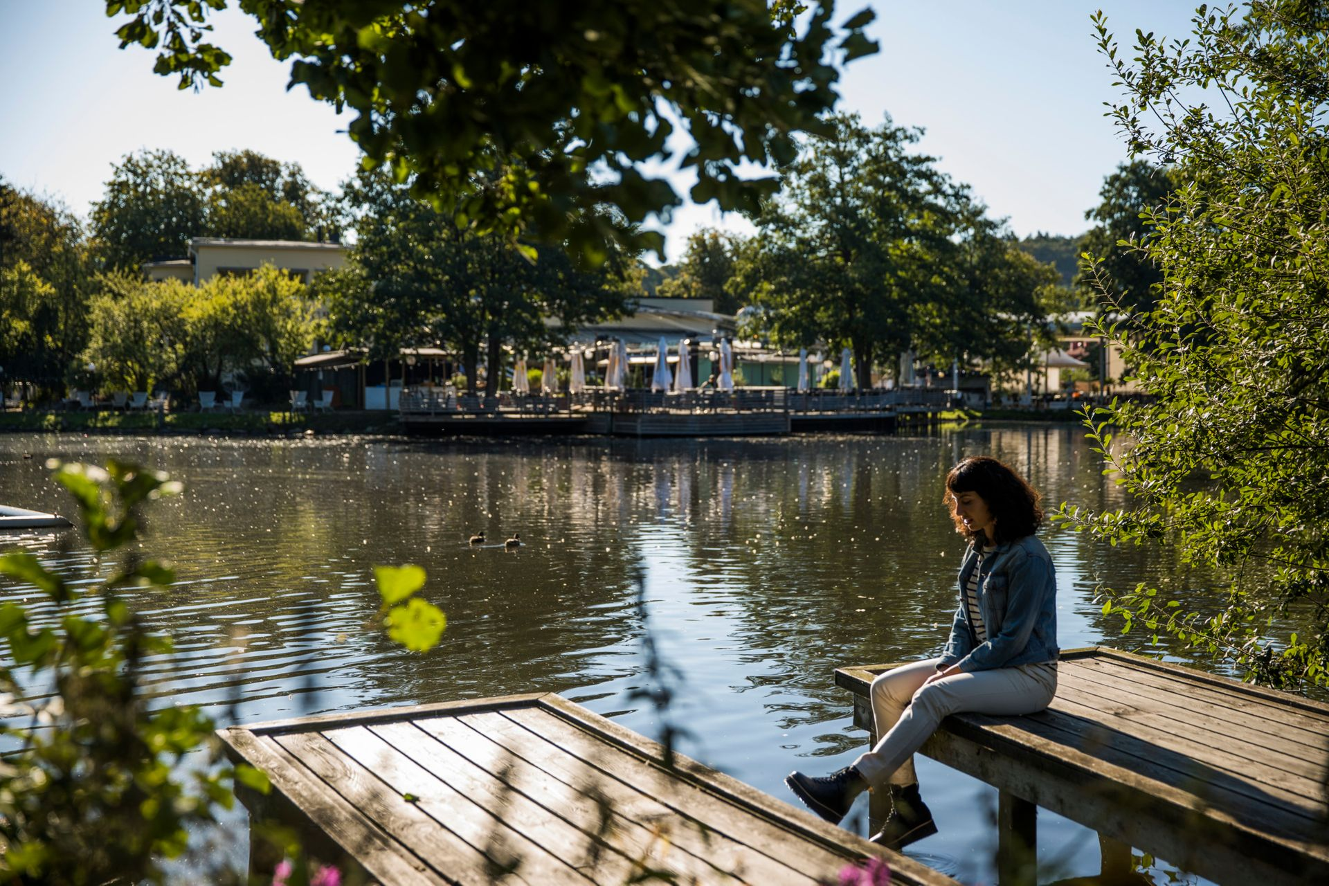 A girl sitting on a deck above water, in one of the biggest parks of Gothenburg
