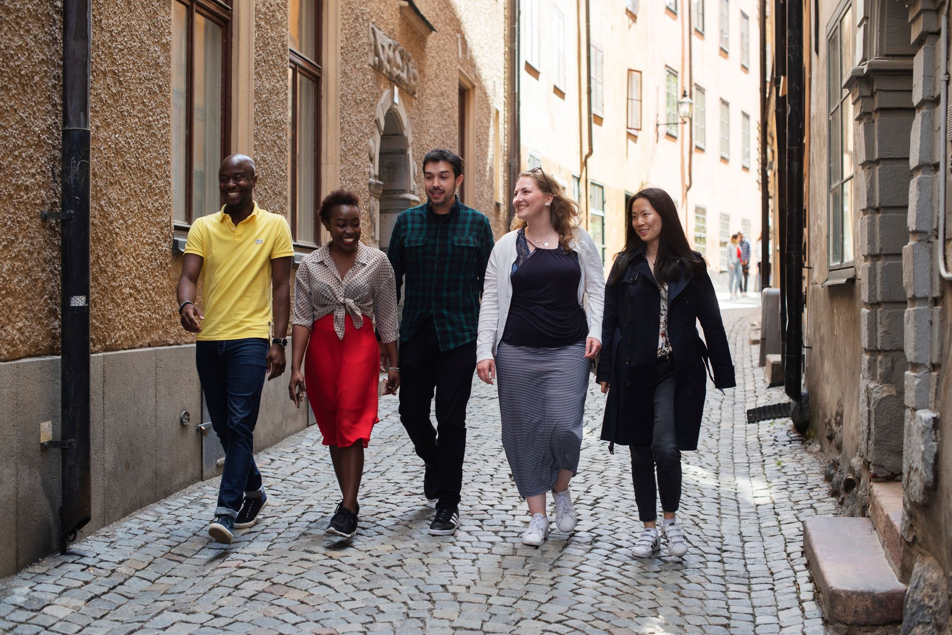 A group of friends are walking down a narrow cobbled street, smiling.