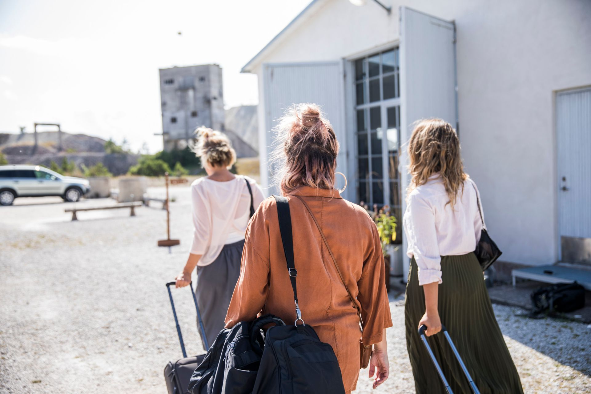Three women with suitcases walk on a parking lot outside a hotel.
