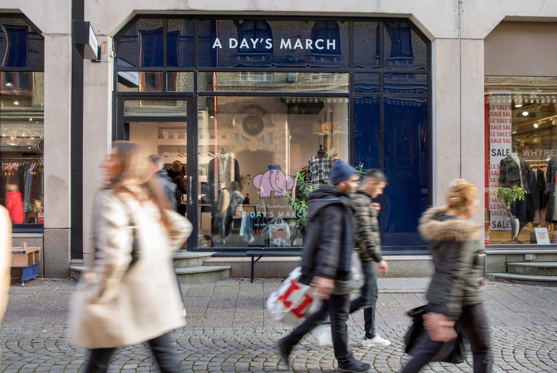 Several people seen blurry walking on a pedestrian shopping street.