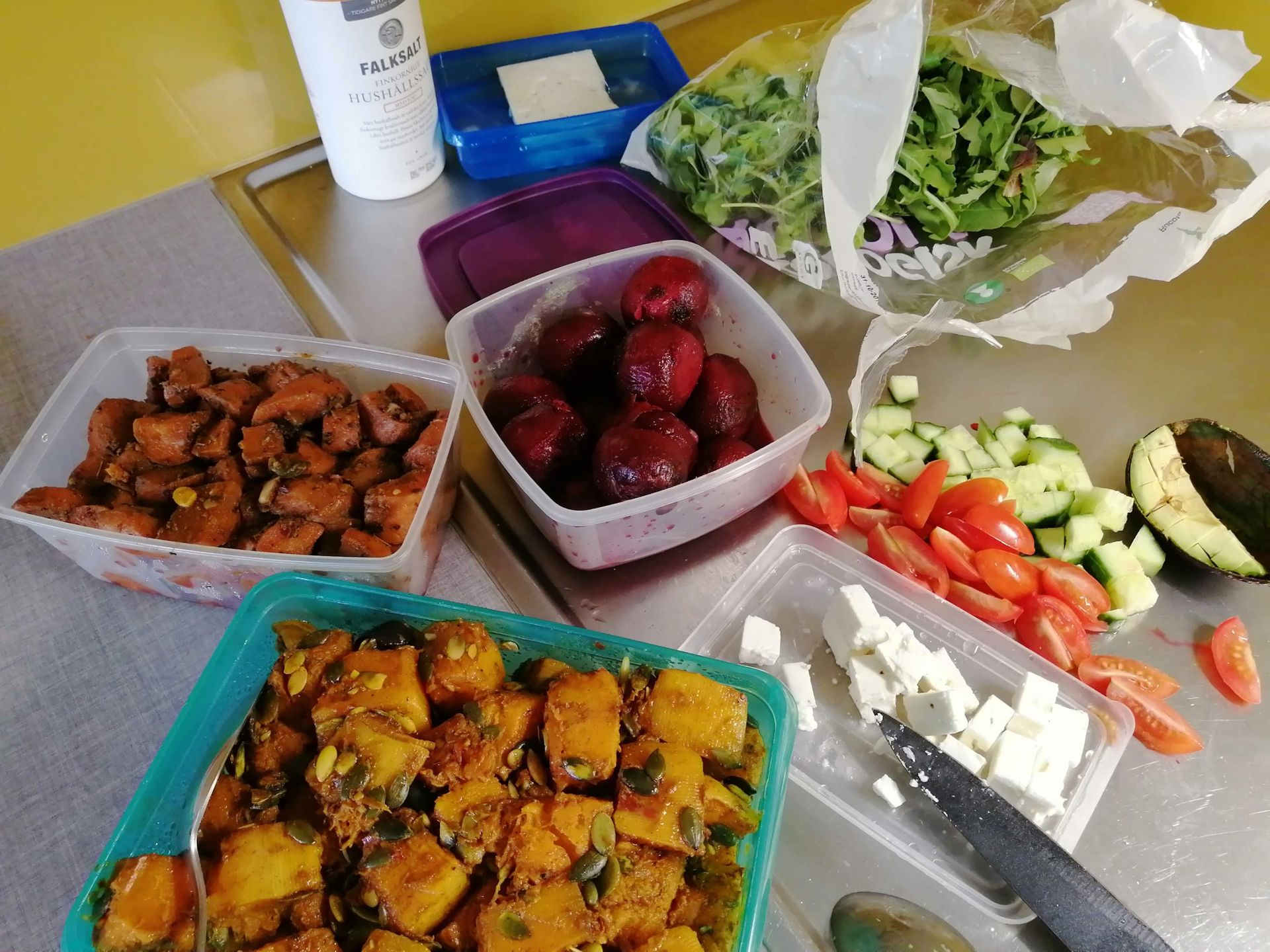 An assortment of cooked and raw vegetables on a kitchen counter, prepared to make a salad