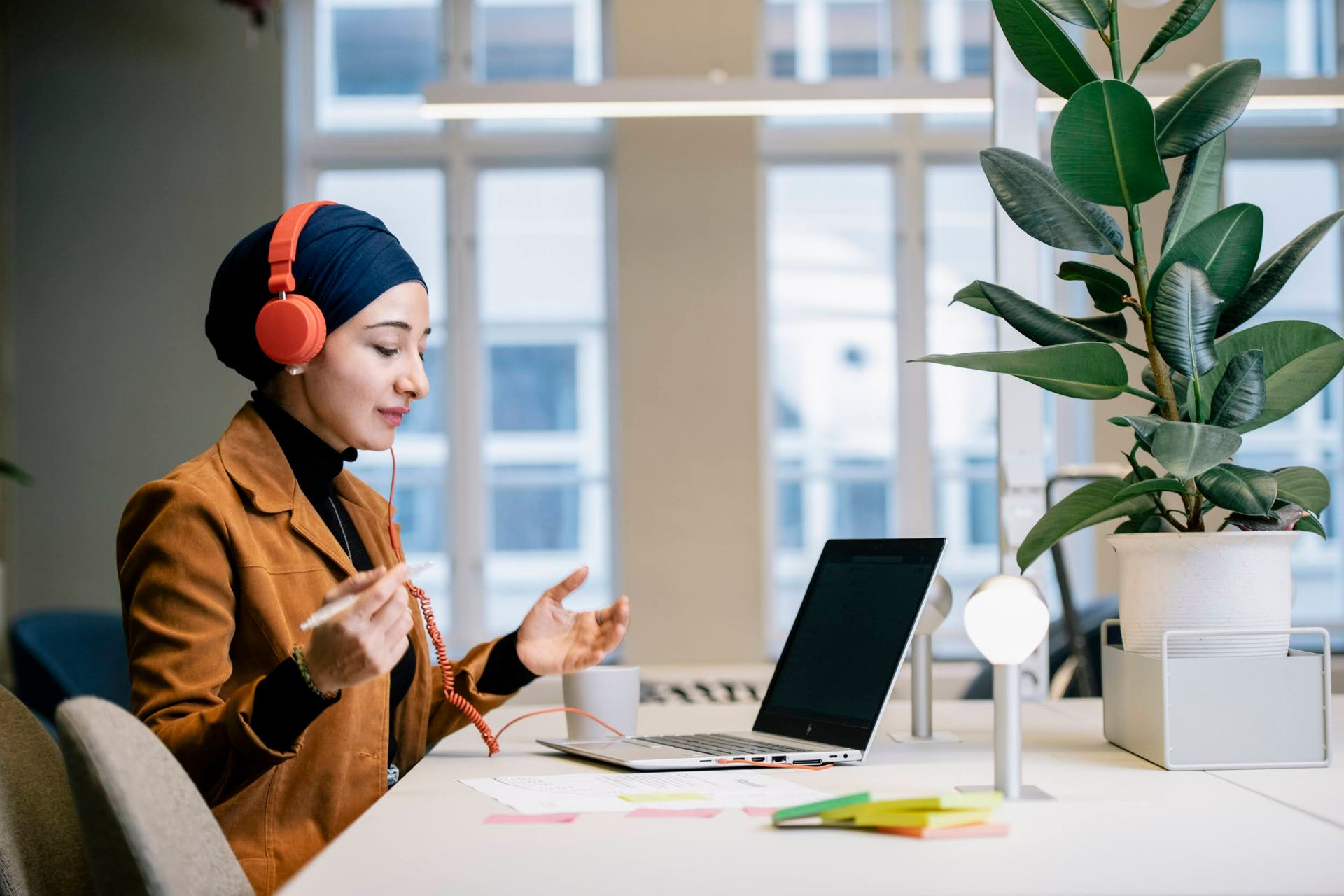 A young woman wearing headphones over a hijab, sitting a a desk and working in front of a laptop